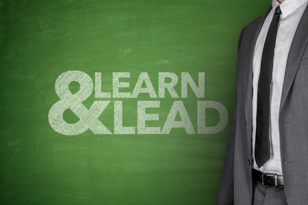 learn and lead: Businessman front of Blackboard with text learn - lead Stock Photo