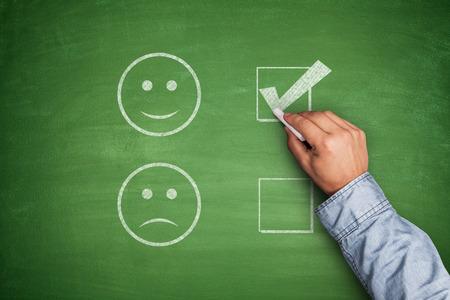 Positive Feedback on green blackboard with hand 스톡 콘텐츠
