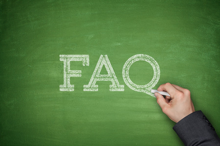 FAQ text concept on green blackboard with hand photo