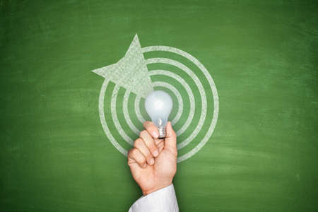 financial target: Dartboard and arrow on green blackboard with light bulb Stock Photo