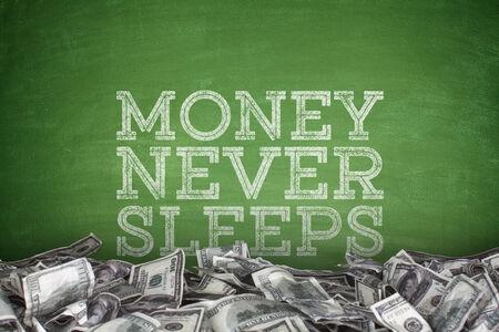 Money never sleeps with pile of dollar bills on green blackboard background