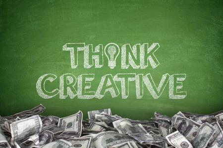 Think creative on blackboard with pile of dollar bills photo