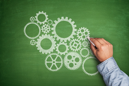 Cogwheels concept on green blackboard with hand Stock Photo