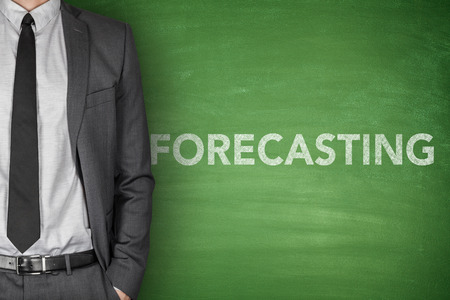 Forecasting concept on green blackboard with businessman