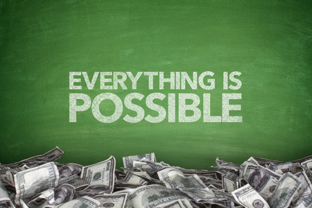 Everything is possible on blackboard with pile of dollars photo