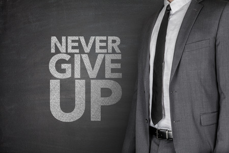 Never give up on blackboard with businessman Banque d'images
