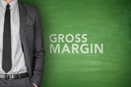 margen: Texto del margen bruto en la pizarra verde con el empresario