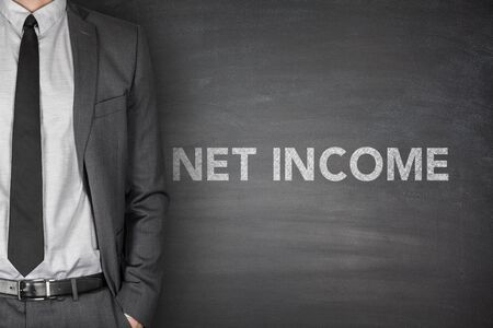 net income: Net income text on black blackboard with businessman