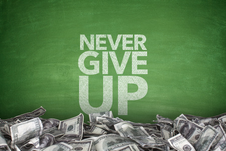 give up: Never give up on blackboard with pile of dollars Stock Photo