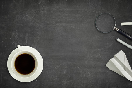Black vintage full frame blank blackboard with coffee cup and magnifying glass Stock Photo