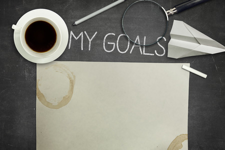 setting goals: My goals concept on black full frame blank blackboard with coffee cup. empty paper and magnifying glass Stock Photo
