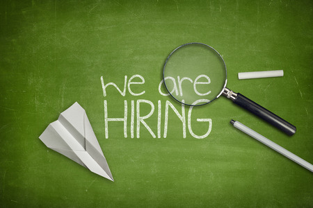 We are hiring concept on green full frame blackboard with magnifying glass Standard-Bild