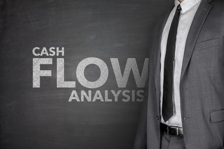 net income: Cash flow analysis on black blackboard with businessman Stock Photo