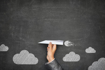 사업가 손없는 프레임과 몇 구름 빈티지 풀 프레임 검은 색 빈 칠판의 전면에 종이 비행기를 들고 스톡 콘텐츠