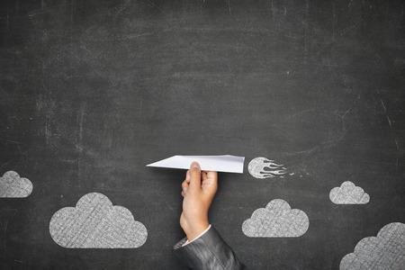 Zakenman hand houden papier vliegtuig op de voorzijde van vintage full frame zwart leeg bord geen frame en paar wolken