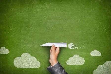 Businessman hand holding paper plane on front of vintage full frame green blank blackboard no frame and couple clouds