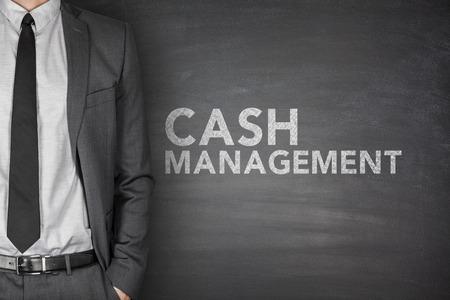 Cash management on black blackboard with businessman Foto de archivo