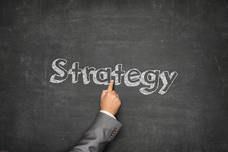 Strategy concept on black blackboard with businessman hand holding paper plane photo