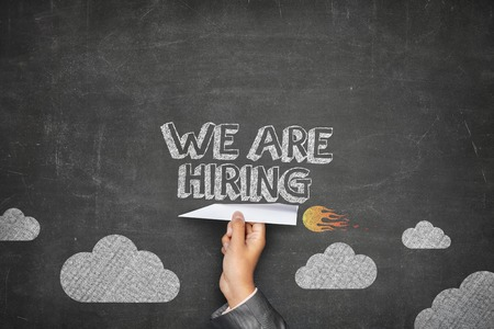 We are hiring concept on black blackboard with businessman hand holding paper plane