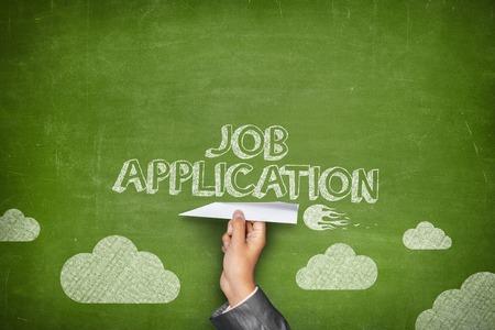 Job application concept on green blackboard with businessman hand holding paper plane Standard-Bild