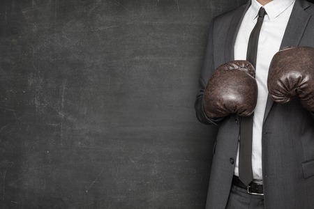 boxing sport: Businessman in boxing gloves and suit on blackboard background Stock Photo