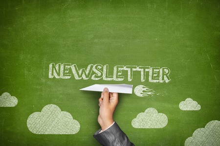 greem: Newsletter concept on greem blackboard with businessman hand holding paper plane