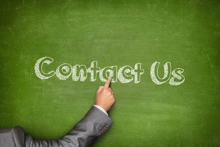online service: Contact us concept on green blackboard with businessman hand pointing Stock Photo