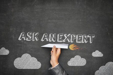 Ask an expert concept on black blackboard with businessman hand holding paper plane