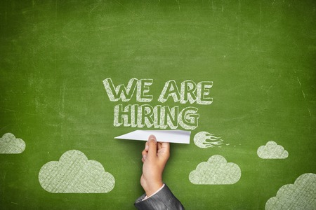 We are hiring concept on green blackboard with businessman hand holding paper plane