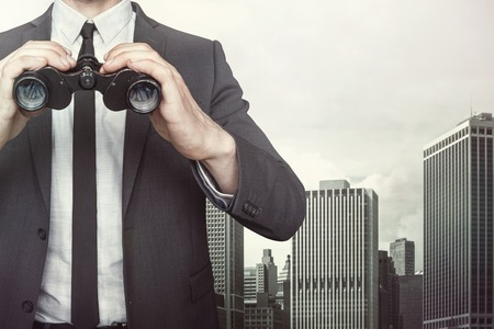 binoculars: Businessman holding binoculars with tie and shirt on cityscape background