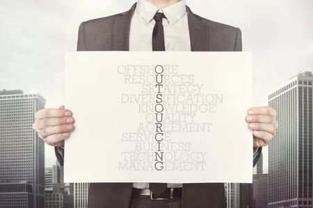 offshoring: Outsourcing crossword concept on paper what businessman is holding on cityscape background Stock Photo
