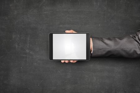 blank tablet: Businessman hand holding tablet front of empty blackboard