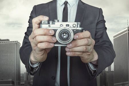 vintage camera: Businessman taking a photo with vintage camera on cityscape background