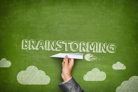 개념: 사업가 손을 잡고 종이 비행기와 녹색 칠판에 개념을 브레인 스토밍