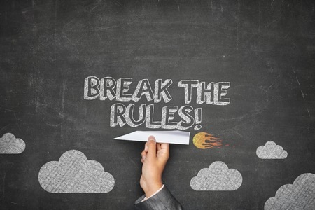 breaking the rules: Break the rules concept on black blackboard with businessman hand holding paper plane Stock Photo