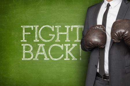 Fight back on blackboard with businessman on side wearing boxing gloves Banco de Imagens - 41813477