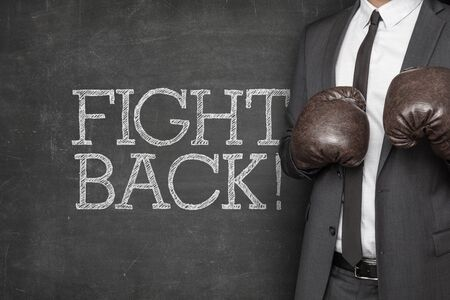 unfairness: Fight back on blackboard with businessman on side wearing boxing gloves Stock Photo