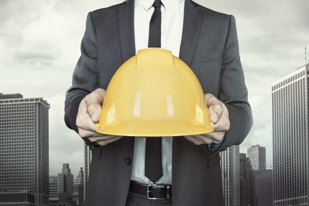 executive helmet: Businessman holding yellow helmet in hands with tie and shirt on cityscape background