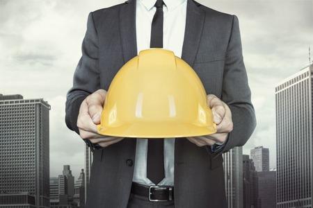 Zakenman die gele helm in handen met das en overhemd op stadsgezicht achtergrond
