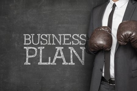 unfairness: Business plan on blackboard with businessman on side wearing boxing gloves Stock Photo