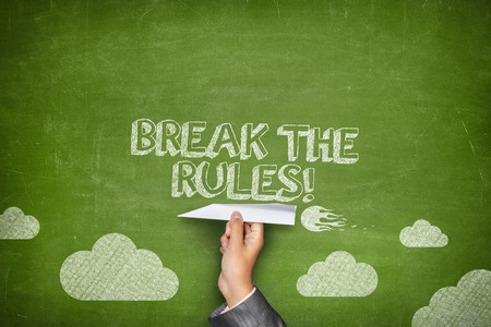 Break the rules concept on green blackboard with businessman hand holding paper plane