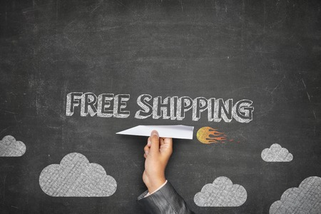 Free shipping concept on black blackboard with businessman hand holding paper plane