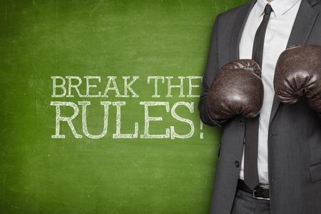 break the rules: Break the rules on blackboard with businessman wearing boxing gloves