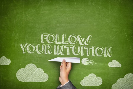 Follow your intuition concept on green blackboard with businessman hand holding paper plane
