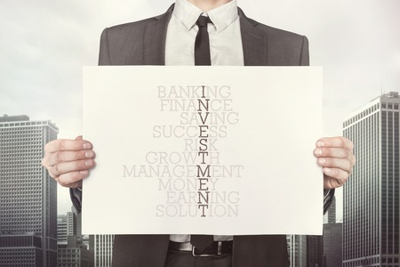 investmen: Investmen crossword concept on paper what businessman is holding on cityscape background Stock Photo