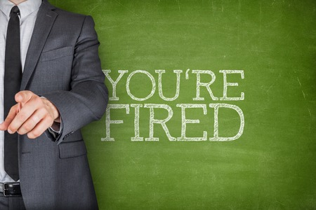 Youre fired on blackboard with businessman finger pointing