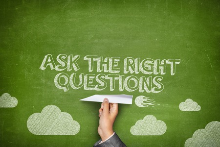 question concept: Ask the right questions concept on green blackboard with businessman hand holding paper plane