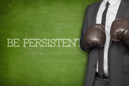 relentless: Be focused on blackboard with businessman wearing boxing gloves Stock Photo