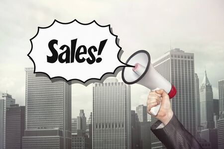 holds: Sales text on speech bubble with megaphone which businessman holds on cityscape background
