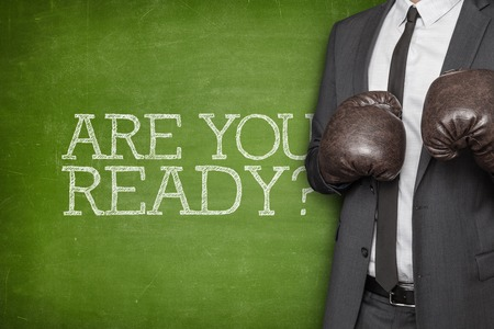 Are you ready on blackboard with businessman wearing boxing gloves